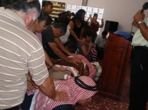 Hermanos nazarenos imponen manos sobre los Misioneros de Proyectos Isaías y Caleb en el culto misionero al regresar del campo