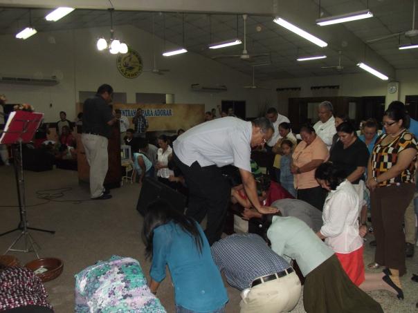 Dr. Carlos Saenz ora por los nazarenos que respondieron al llamado de Dios durante el servicio de entrega en San Pedro Sula, Honduras