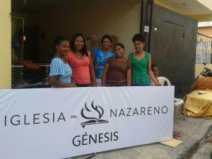 Mujeres de Haina colaborando con la instalación del rótulo